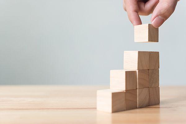 Hand baut Stufen aus Holzbausteinen