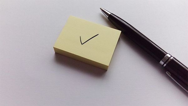 Checkmark on notepad and pen next to it