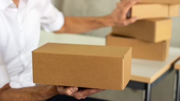 Person presents cardbord box and pushes away other boxes